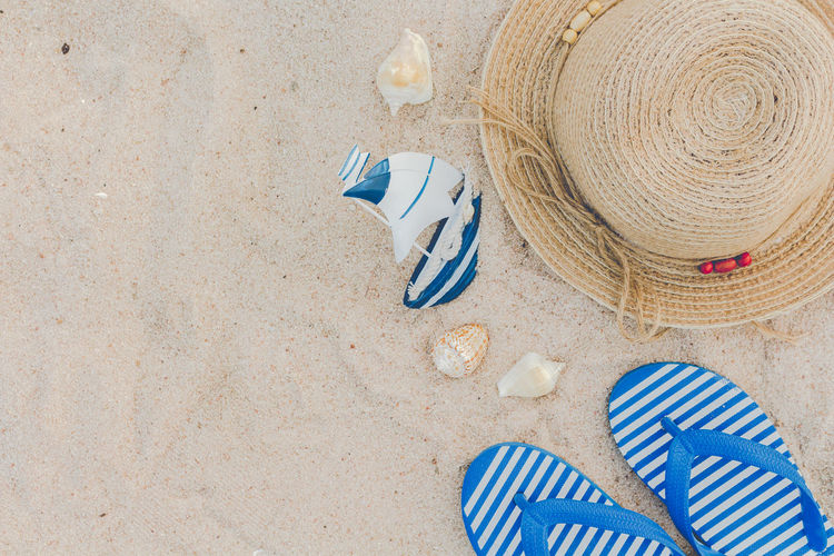 Straw hat and flip flops on a tropical beach Beach Blue Clothing Day Hat High Angle View Holiday Land Nature No People Outdoors Personal Accessory Sand Sandal Shoe Slipper  Still Life Straw Hat Striped Summer Sun Hat Trip Vacations