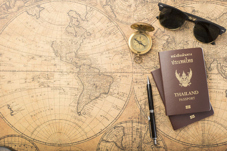 High angle view of passport with pen and sunglasses on map