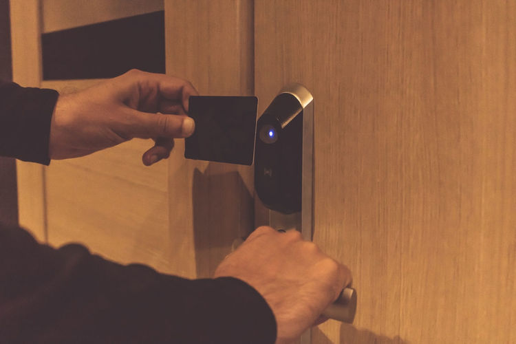 Cropped hands of man using cardkey on door