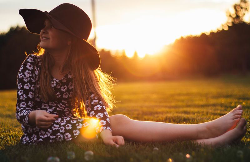Smiling Girl Wearing Hat Sitting On Grassy Field During Sunset