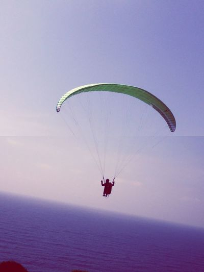 Paraglider over sea against clear sky