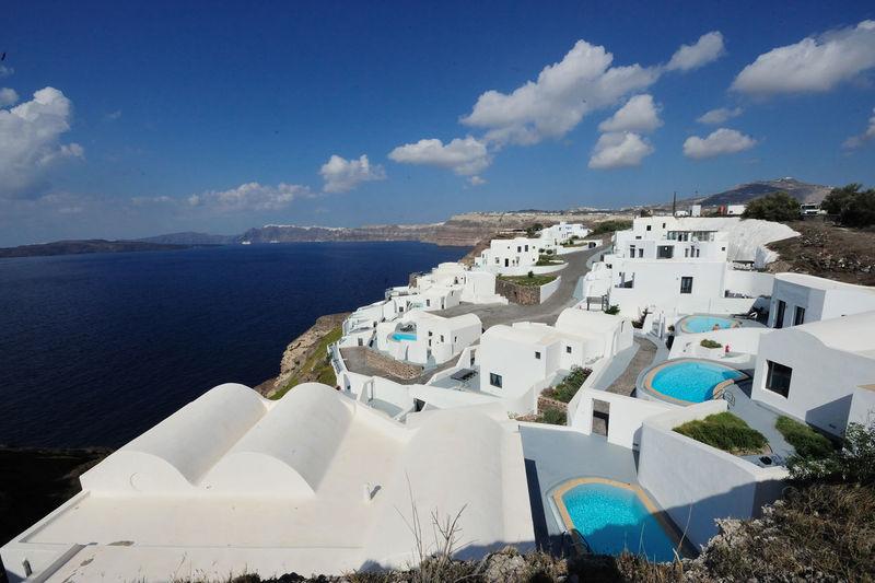 Houses at santorini by aegean sea against sky