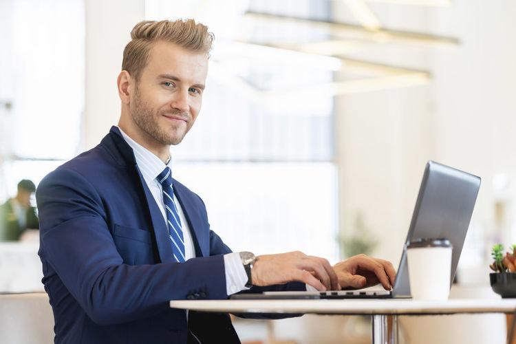 Portrait of businessman using laptop at cafe