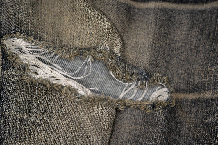 Close-up pictures of the surface of the old jeans fabric and the tear mark