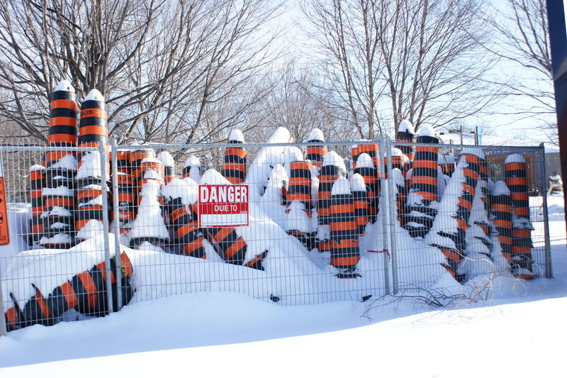 Snow Covered Traffic Cones In Fence With Warning Sign