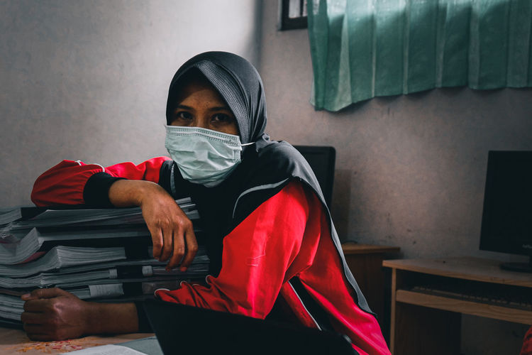Portrait of woman wearing face mask sitting at desk