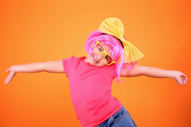 Portrait of woman with pink hair standing against orange background