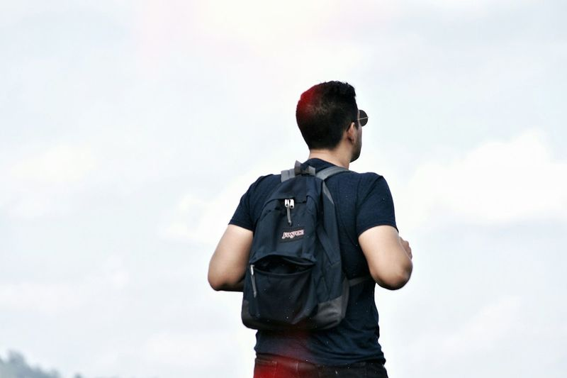 Rear view of boy standing against sky