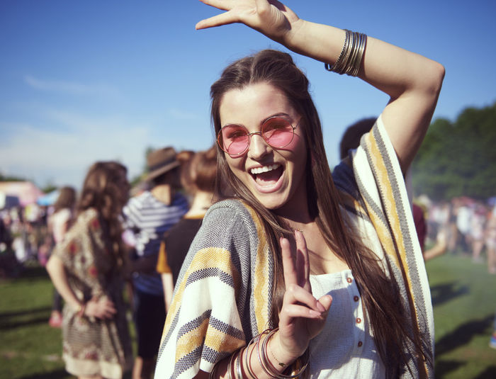 Portrait of cheerful young woman dancing in party during sunny day