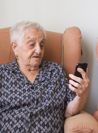 Close-up of senior woman using mobile phone while sitting on sofa