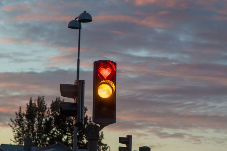 Low Angle View Of Illuminated Traffic Signal Against Cloudy Sky