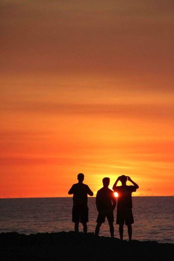 The kids enjoy the vastness of our world Sunset Horizon Over Water Standing Orange Color Beach Men Rear View Water Togetherness Sky Friendship Beauty In Nature Outdoors