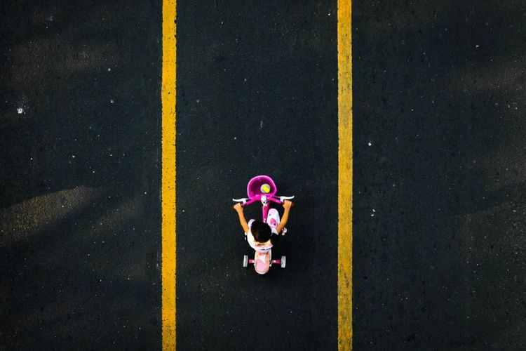 High angle view of girl riding bicycle on road
