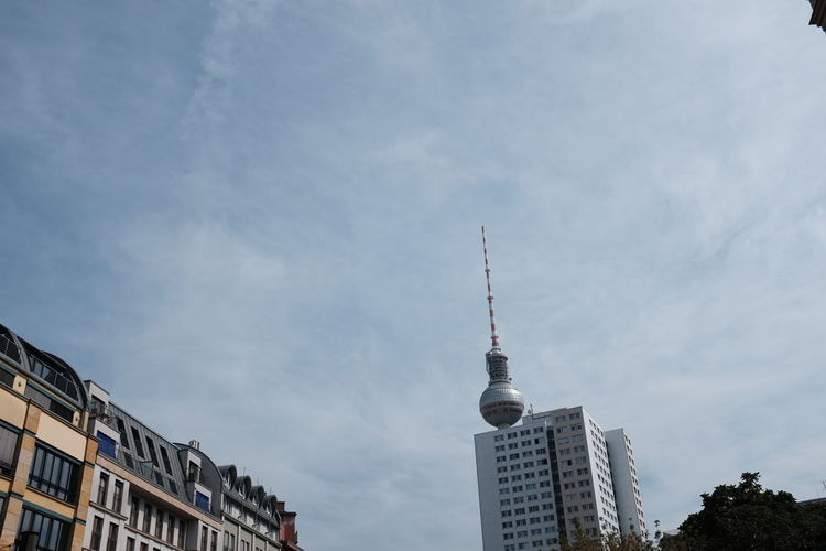 Low angle view of fernsehturm and buildings against sky