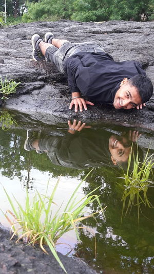 Portrait of young man lying on rock by pond