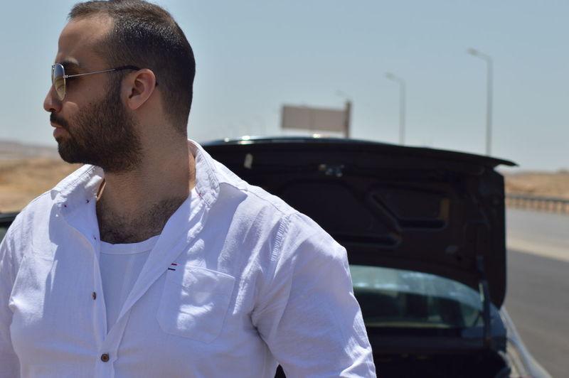Man wearing sunglasses against car breakdown