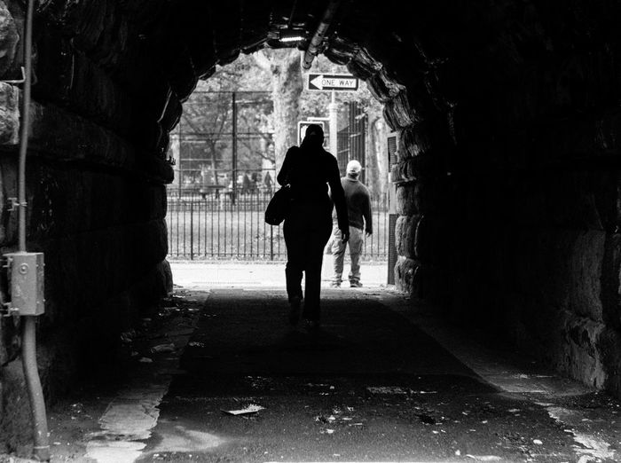 Rear view of silhouette woman standing in tunnel