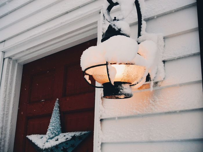Low Angle View Of Snow Covered Illuminated Lamp Mounted On House