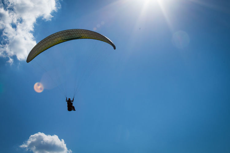 Paragliding over blue sky Blue Sky Clouds Day Extreme Sports Flying Outdoors Paragliding People Sky Sun