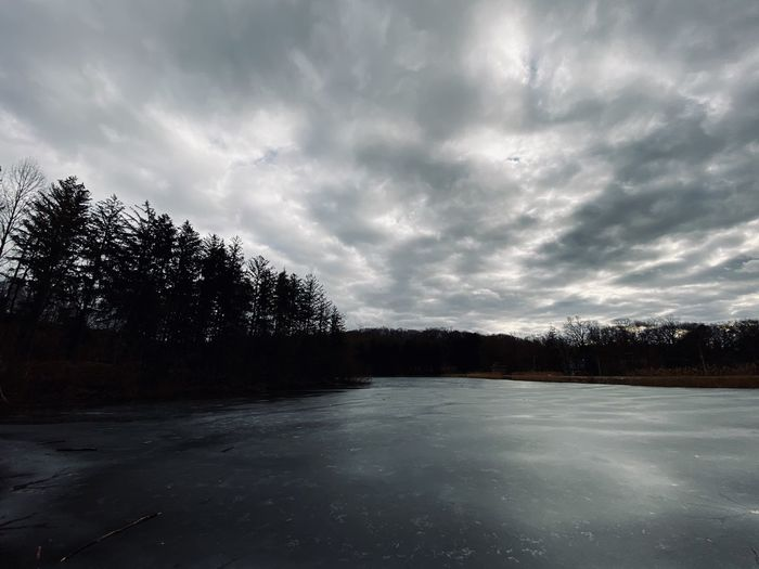 Scenic view of lake against sky during winter