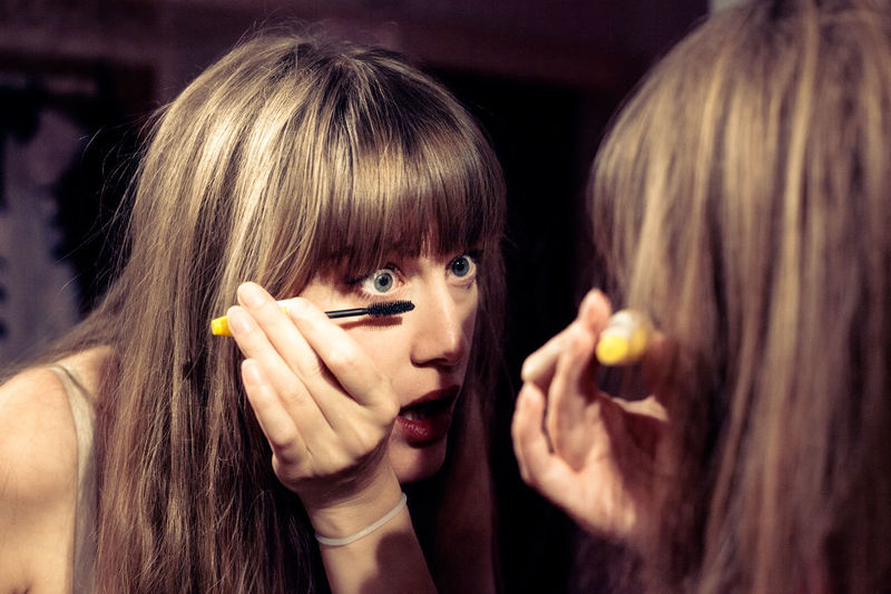 Woman applying mascara at home