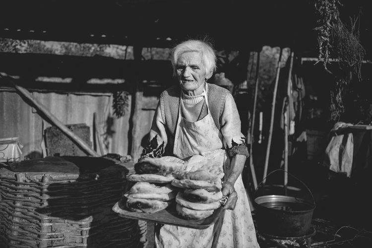 Senior woman carrying tray of baked breads