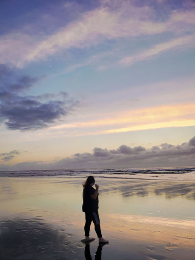 Full length of woman standing at beach against sky during sunset
