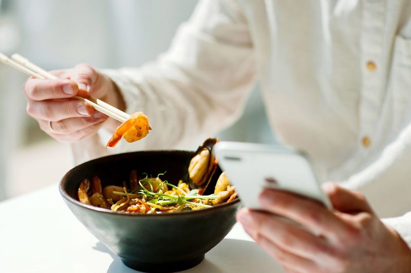 Midsection of person holding food and phone in restaurant