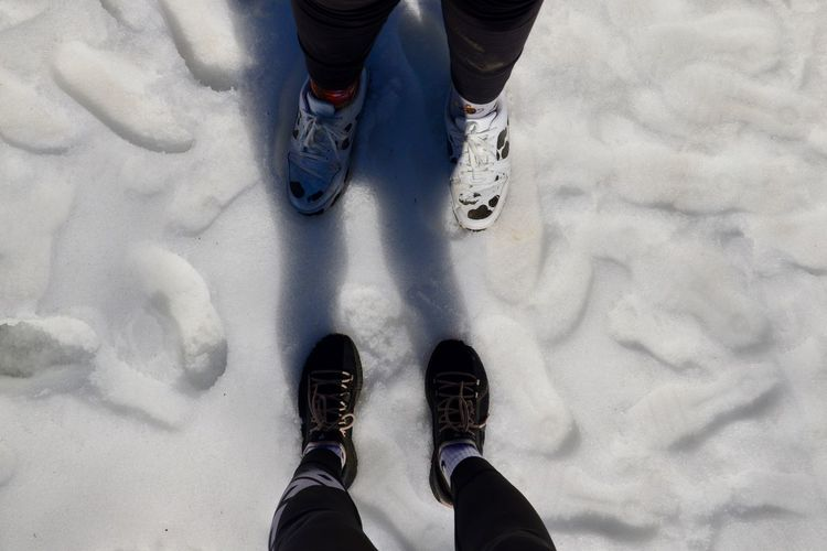 Low section of people standing on snow