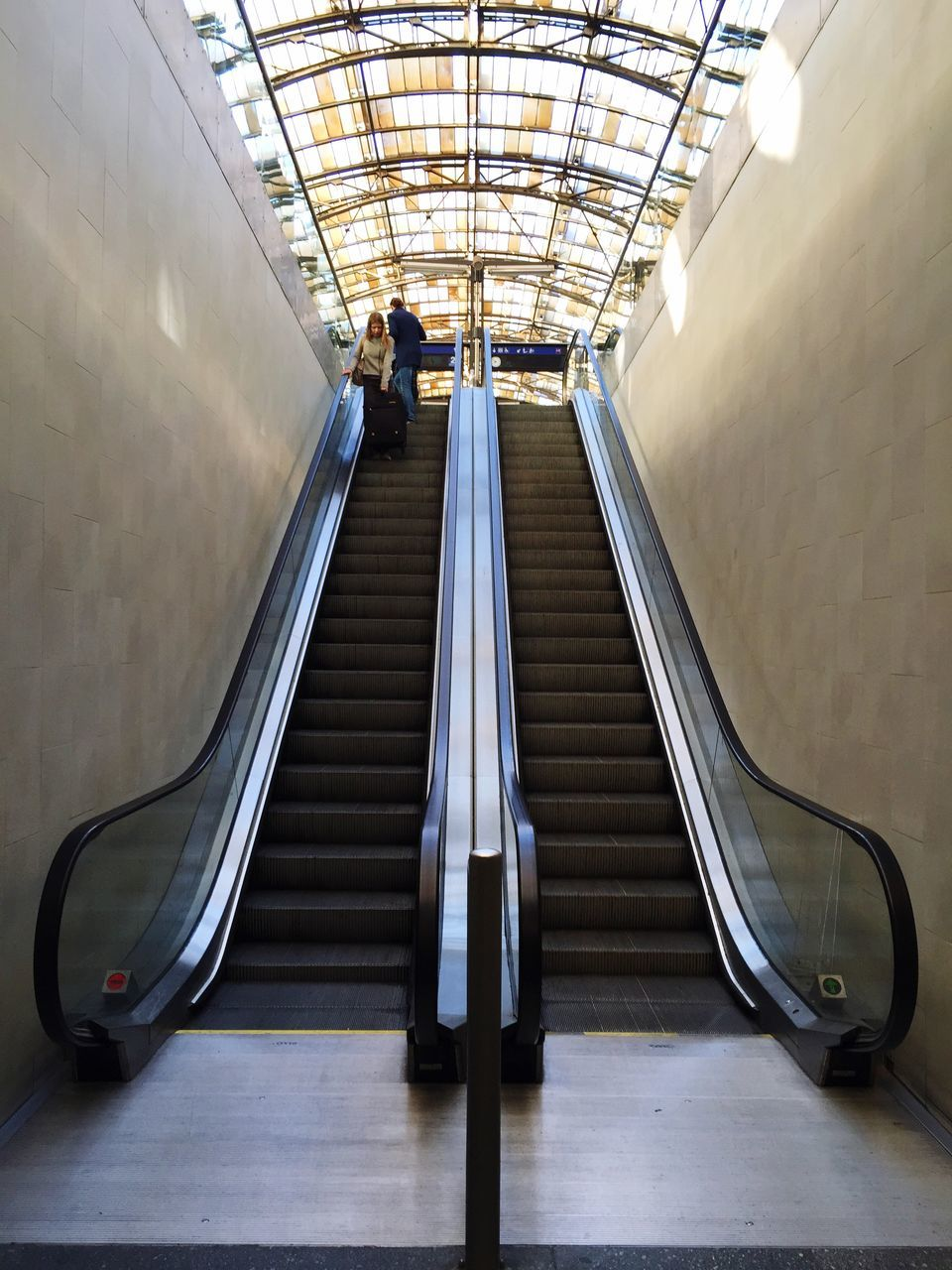 steps and staircases, steps, staircase, indoors, railing, escalator, real people, the way forward, illuminated, architecture, convenience, built structure, low angle view, full length, one person, modern, hand rail, day, people