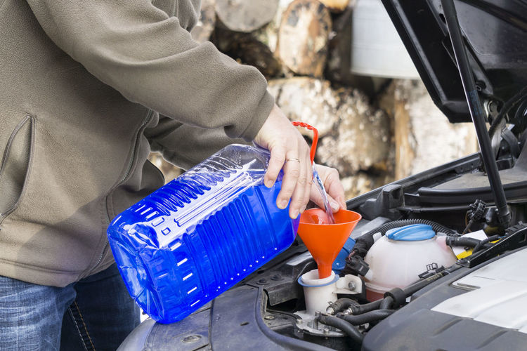 Windshield washer fluid being poured into a vehicle's storage tank Close-up Human Hand One Person Outdoors Poured Vehicle's Storage Tank Washer Fluid Windshield
