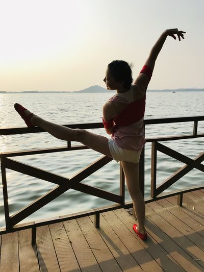 Rear view of ballet dancing on pier against sea