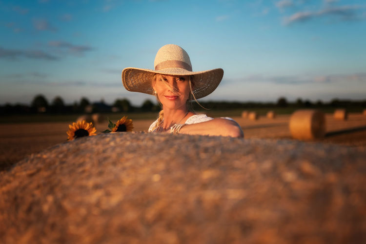 Woman wearing hat on field against sky during sunset
