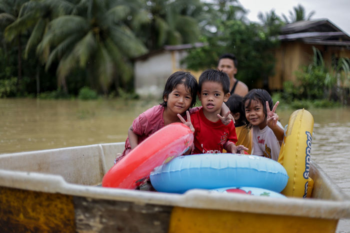 flood victims at kelantan Boys Casual Clothing Childhood Day Elementary Age Enjoyment Family Father Flood Victims Fun Girls Happiness Leisure Activity Lifestyles Looking At Camera Mature Women Mother Outdoors Real People Sitting Smiling Son Togetherness Young Adult Young Women