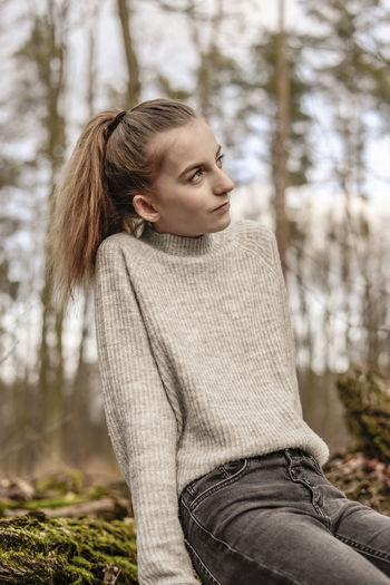 Teenage girl looking away while sitting in forest