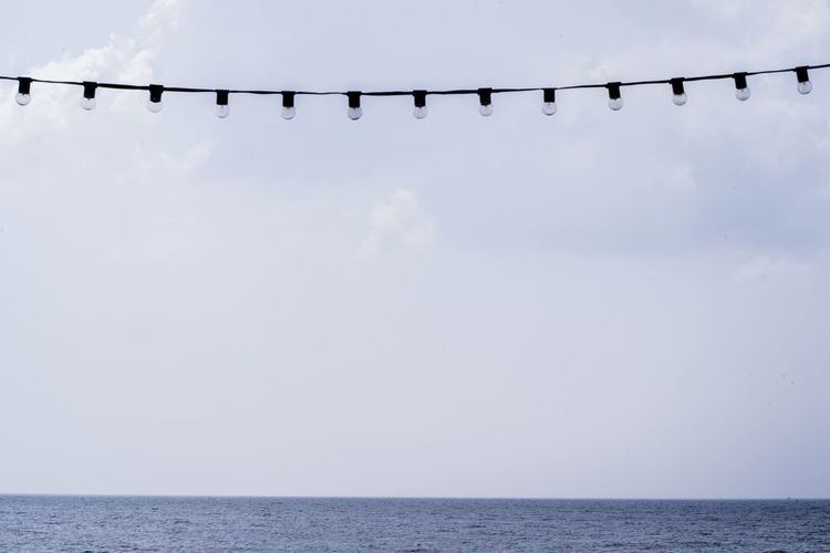 Low angle view of light bulbs hanging over sea against sky