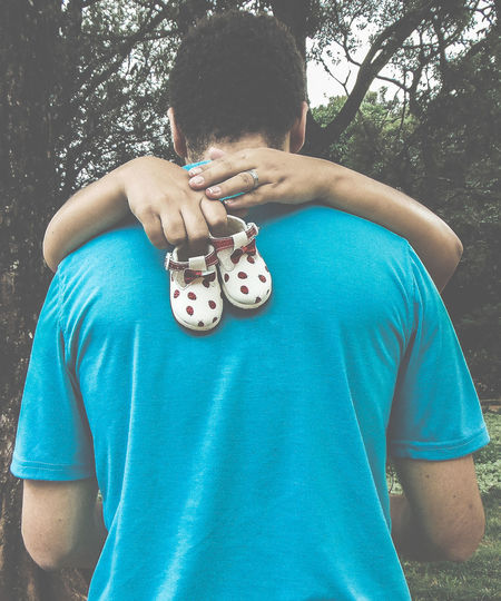 Woman hugging man while holding baby booties at forest