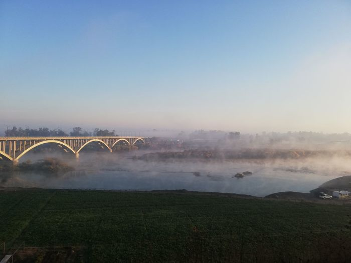 Arch bridge over field against sky during foggy weather