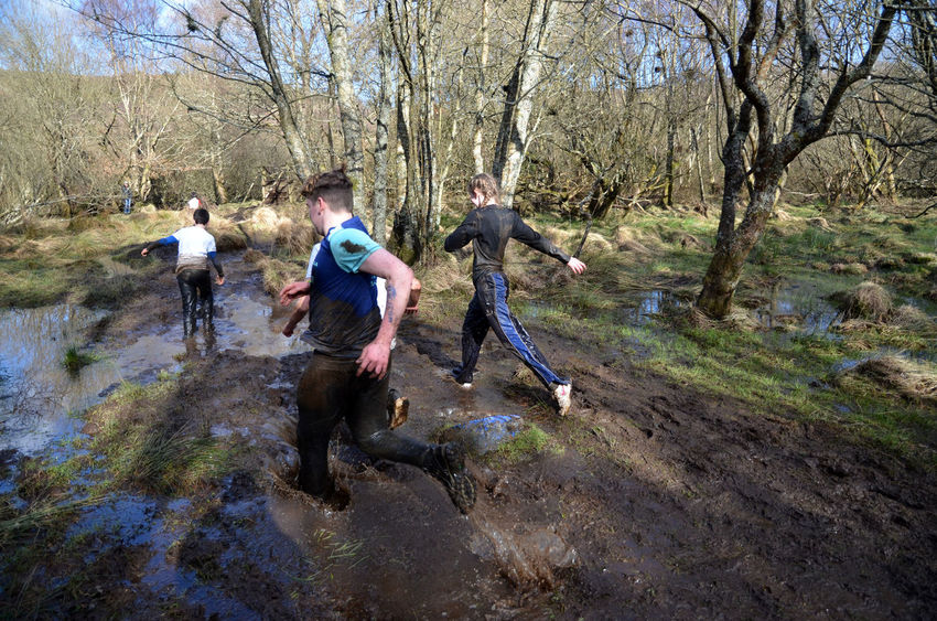 Running Activity Bare Trees Dirt Forest Group Of People Leisure Activity Motion Mud Muddy Outdoors Race Splash Young People