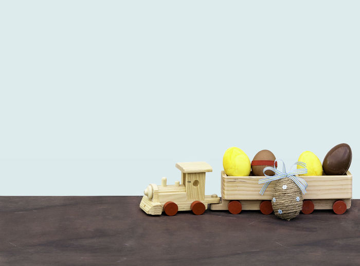 A little wood train with red wheels bringing colorful easter eggs for the holiday. Concept for easter April Celebration Chocalate Easter Faith Family Fun Holiday Hope Jesus Ribbon Tradition Wood Cake Candy Decoration Egg Food Locomotive Resurrection Still Life Surprise Sweet Traditional Train