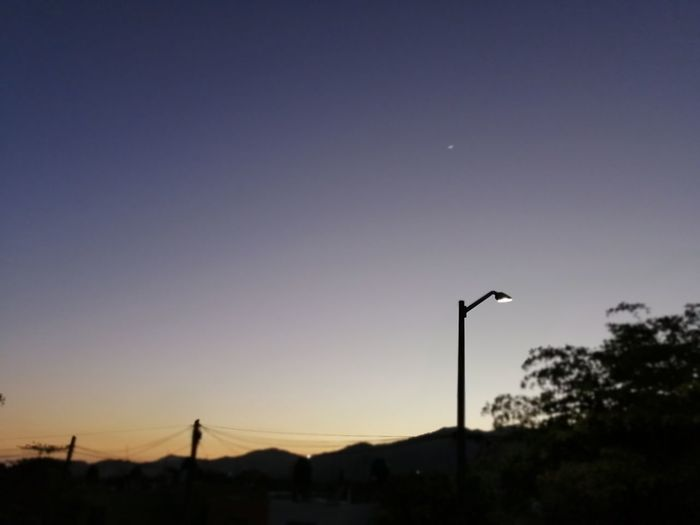Street light against clear sky at sunset