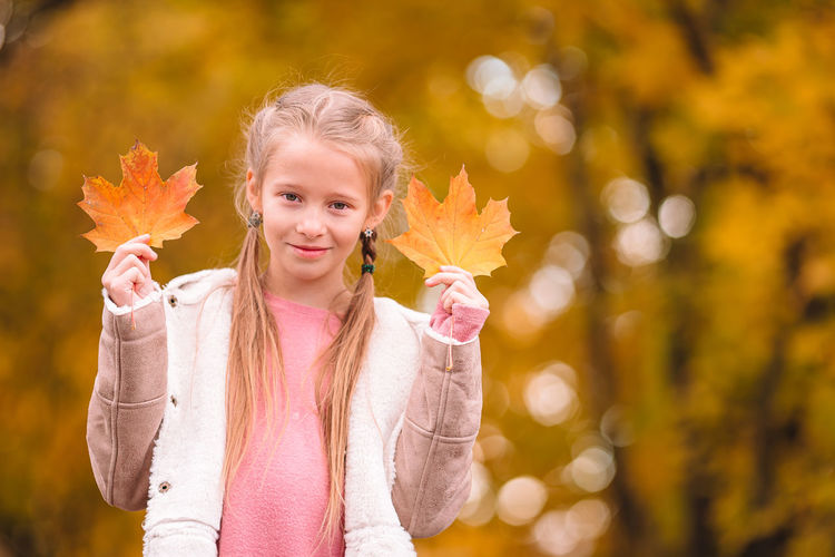 Portrait of girl standing on leaves during autumn
