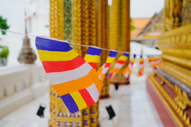 Close-up of multi colored buddhist flags hanging outside building