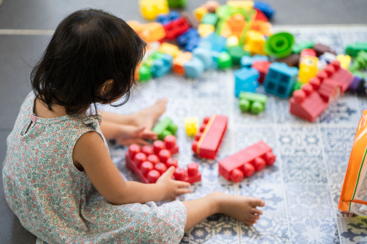 Cute little girl playing plastic building block outdoor.