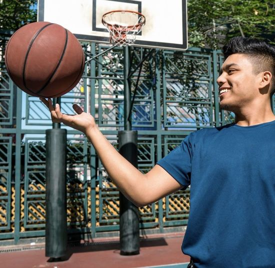 Smiling Man Playing With Ball With Basketball Court