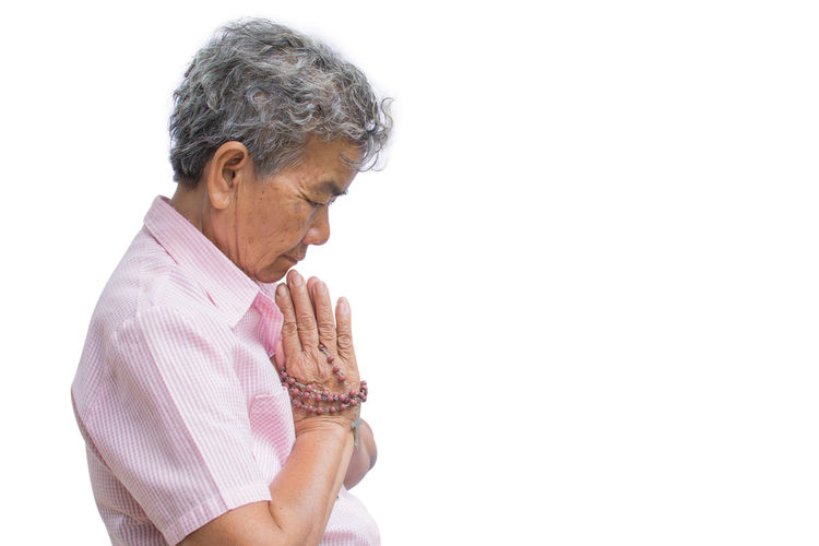 Side View Of Senior Woman With Hands Clasped Praying Against White Background