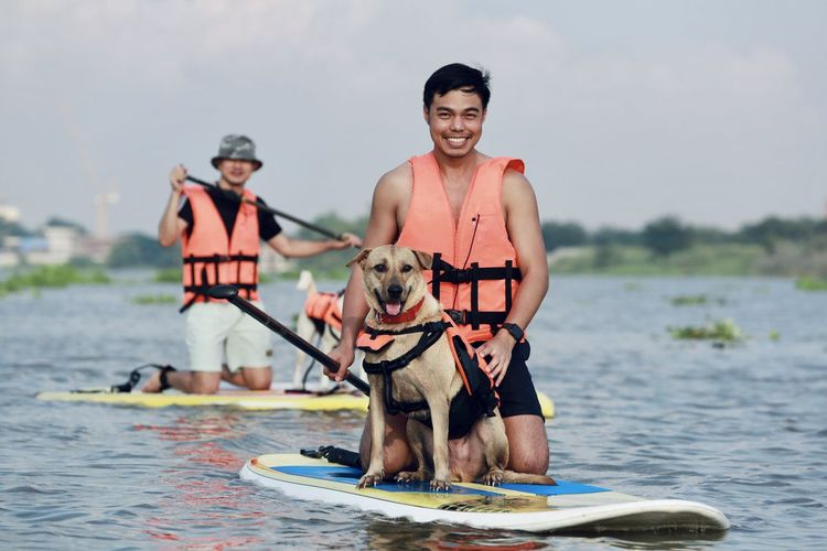 Man with dog standing in sea