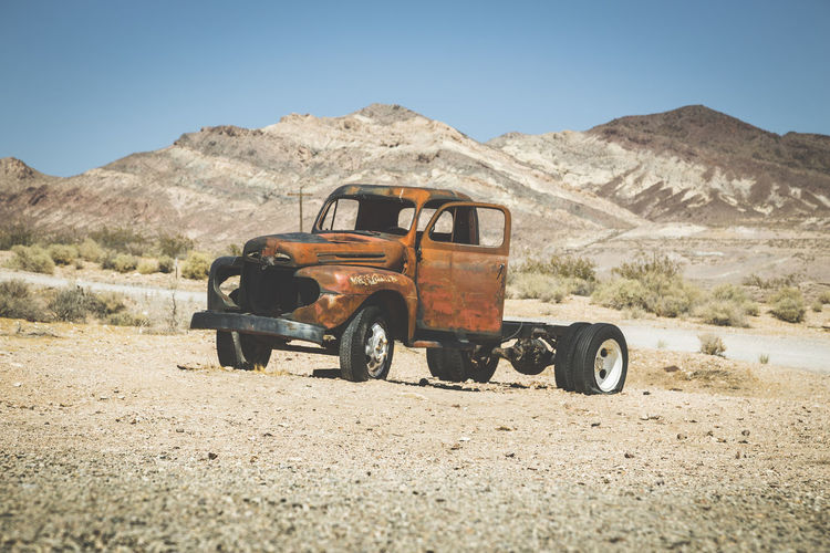 Abandoned truck on land in desert against clear sky