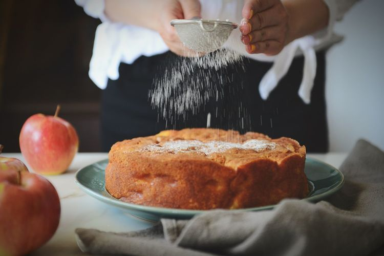 Midsection of person sprinkling powdered sugar on cake at kitchen