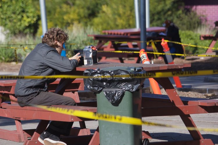 Side view of man sitting at picnic table amidst cordon tape